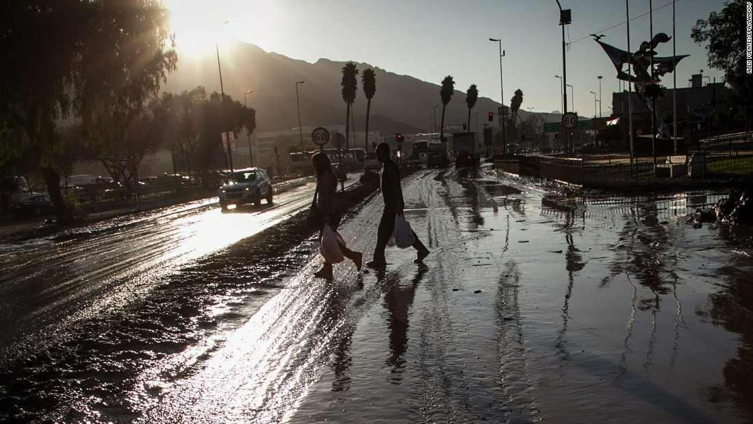 People walk on a street covered with mud in Copiapo, Chile, on Thursday, April 2. Floods in the north of the country have left killed at least 25 people and left more than 100 missing, with death tolls expected to rise.