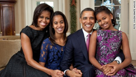 President Barack Obama, first lady Michelle Obama, and their daughters, Malia, 13, (left) and Sasha, 10, sit for a family portrait in the Oval Office, December 11, 2011.