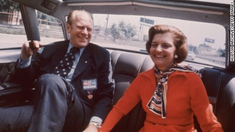 "United States president Gerald Ford and wife Betty Ford sitting in the back seat of a car smiling and holding hands in 1975. Ford's campaign 1976 slogan was ""He's Making us Proud Again."""