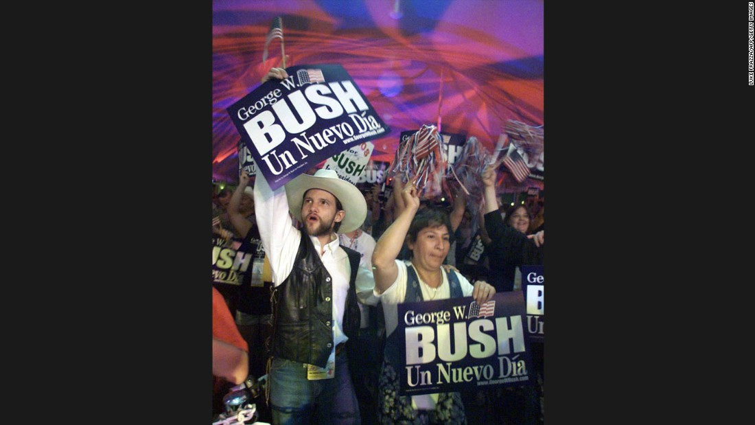 "Hispanic supporters of Bush cheer and hold up a sign that reads ""A New Day"" in Spanish, after the Texas governor won the Republican Party's unofficial ""straw poll"" on August 14, 1999, in Ames, Iowa."