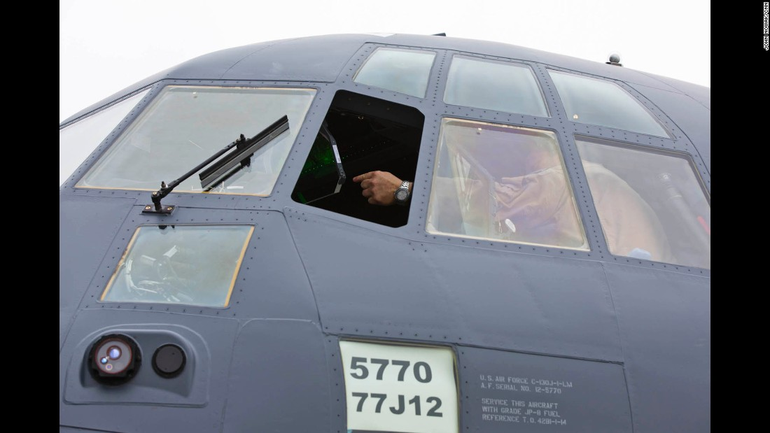 Lockheed Martin pilot Steve Knoblock points out features inside the cockpit of the MC-130J Super Hercules Commando II.