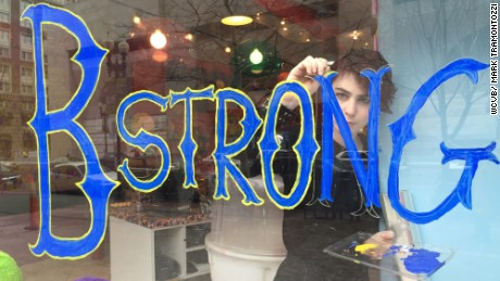 "A worker writes ""B Strong"" on the window of Sugar Heaven, a shop near the Boston Marathon finish line."