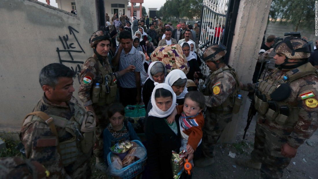 Kurdish Peshmerga forces help Yazidis as they arrive at a medical center in Altun Kupri, Iraq, on April 8.