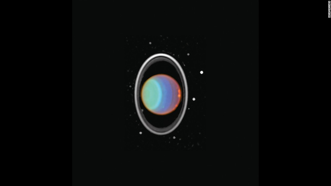 Hubble tracked clouds on Uranus in this image taken in 1997. The image is a composite of three near-infrared images. The planet's rings are prominent in the near infrared. Eight of Uranus' 27 moons can be seen in both images. Uranus is about 1.75 billion miles from Earth.