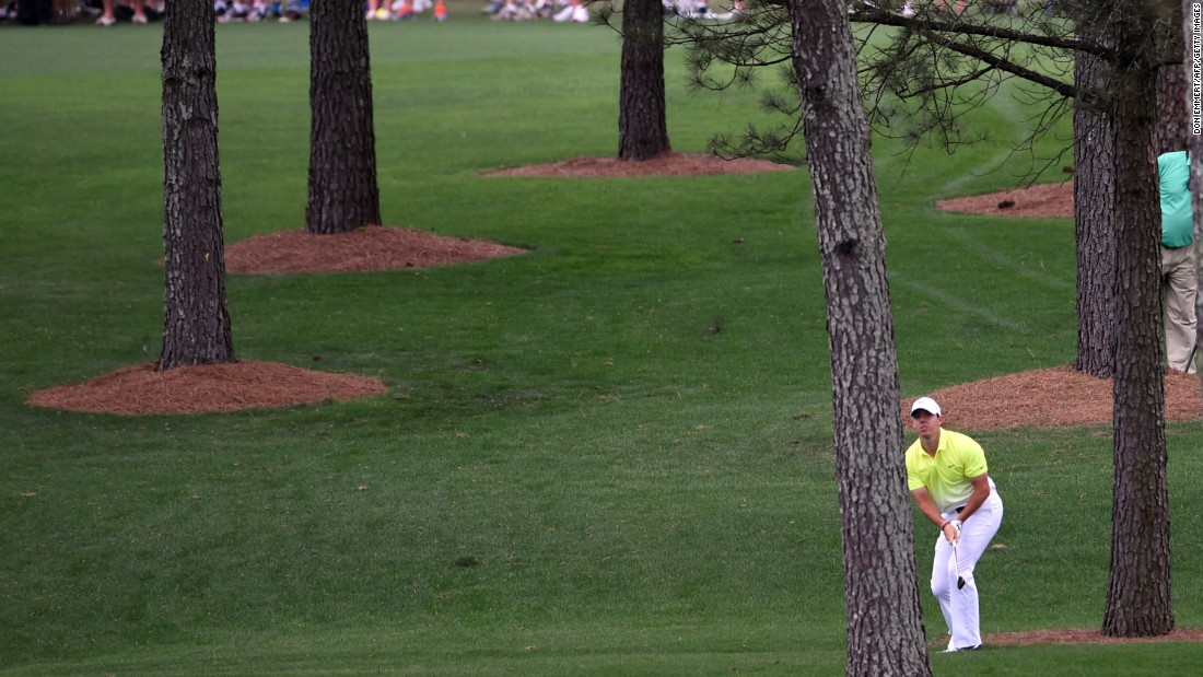 Rory McIlroy hits out of the trees on the seventh hole at Augusta. He birdied the hole and picked up more shots at eight and 11 to continue his bid for a top-five finish.