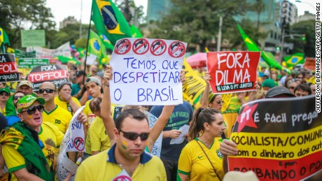 Demonstrators take part in a protest againt Brazilian President Dilma Rousseff in Porto Alegre, Brazil on April 12, 2015. Tens of thousands of Brazilians turned out for demonstrations Sundays to oppose leftist president Dilma Rousseff, a target of rising discontent amid a faltering economy and a massive corruption scandal at state oil giant Petrobras. The signs read 'We have to clear of the PT rats', 'Dilma out and take the PT with you' and 'It is easy to preach to be socialist / communist with the money of others and worse: stealing the people'. AFP PHOTO / Jefferson BERNARDES (Photo credit should read JEFFERSON BERNARDES/AFP/Getty Images)