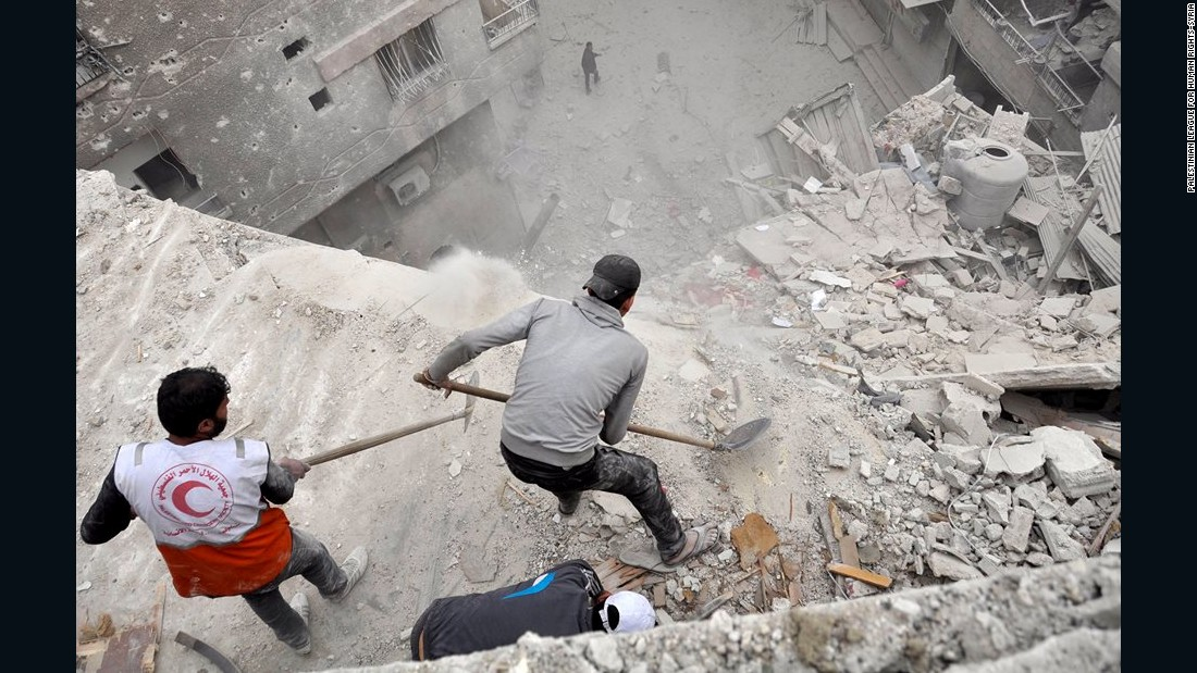Volunteers scoop debris off a building that was hit by a bomb in early April in the Yarmouk Palestinian refugee camp near Damascus, Syria.