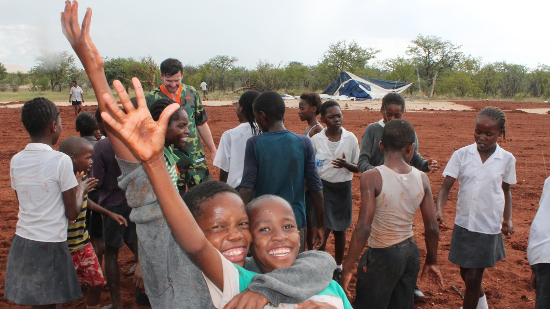 Children from the Okaukuejo school join Global United players for a kickabout, with Gorlitz visible in the background.