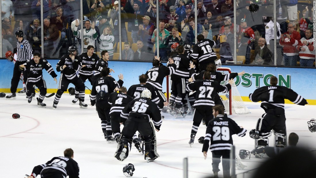 Providence hockey players mob their goalie, Jon Gillies, after they defeated Boston University on Saturday, April 11, to win the school its first hockey championship. Gillies had 49 saves in the 4-3 victory.