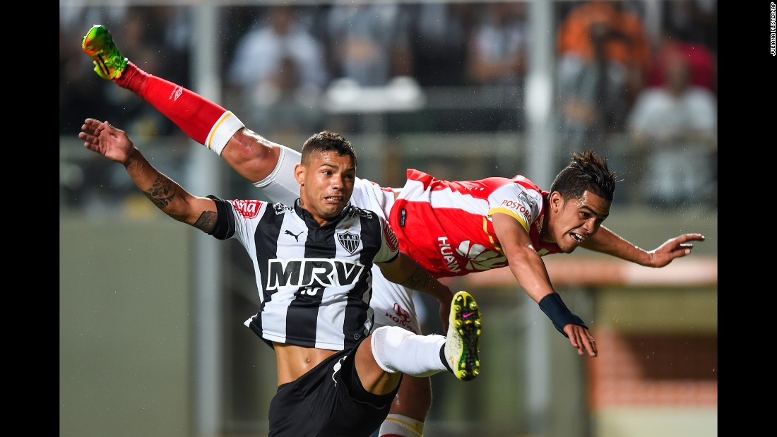 Santa Fe's Jose Anchico, top, falls over Atletico Mineiro's Carlos during a Copa Libertadores match played Thursday, April 9, in Belo Horizonte, Brazil. Carlos scored a goal in the match, which ended 2-0.
