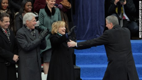 Newly sworn in New York City Mayor Bill de Blasio (R) walks to hug Hillary Rodham Clinton (C) on the steps of City Hall in Lower Manhattan January 1, 2014 in New York. Former US President Bill Clinton (2nd L) and New York State Governor Andrew Cuomo (L) and actress Cynthia Nixon (top row, C) watch.