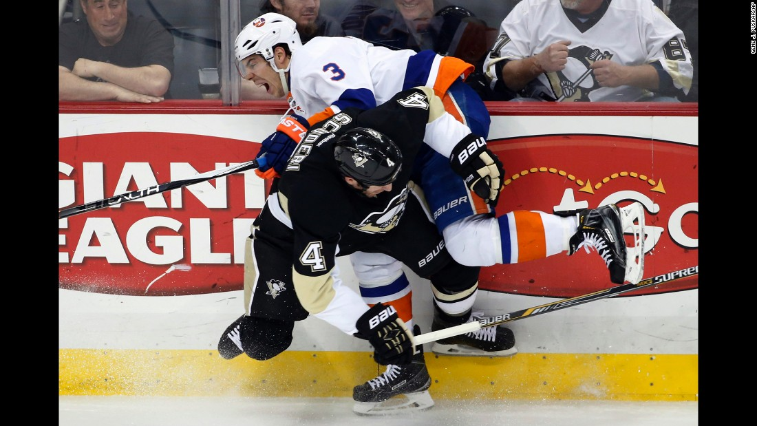 Pittsburgh's Rob Scuderi hip-checks Travis Hamonic of the New York Islanders during an NHL game in Pittsburgh on Friday, April 10.