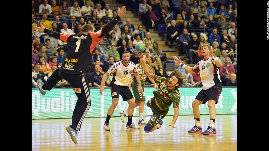 Fredrik Raahauge Petersen, a handball player with the German club Fuchse Berlin, tries to throw the ball past TuS Nettelstedt-Lubbecke's Nikola Blazicko during a match played Wednesday, April 8, in Berlin.