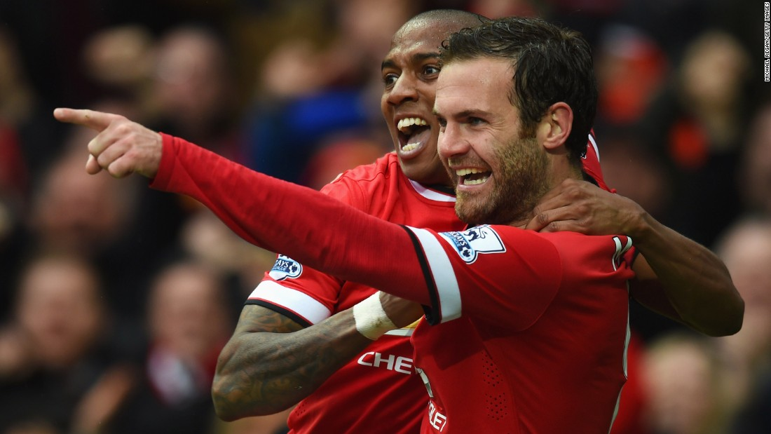 Manchester United's Juan Mata points to a teammate as he and Ashley Young celebrate his goal Sunday, April 12, in Manchester, England. United's 4-2 home victory over Manchester City moved them four points ahead of their crosstown rivals in the Premier League.