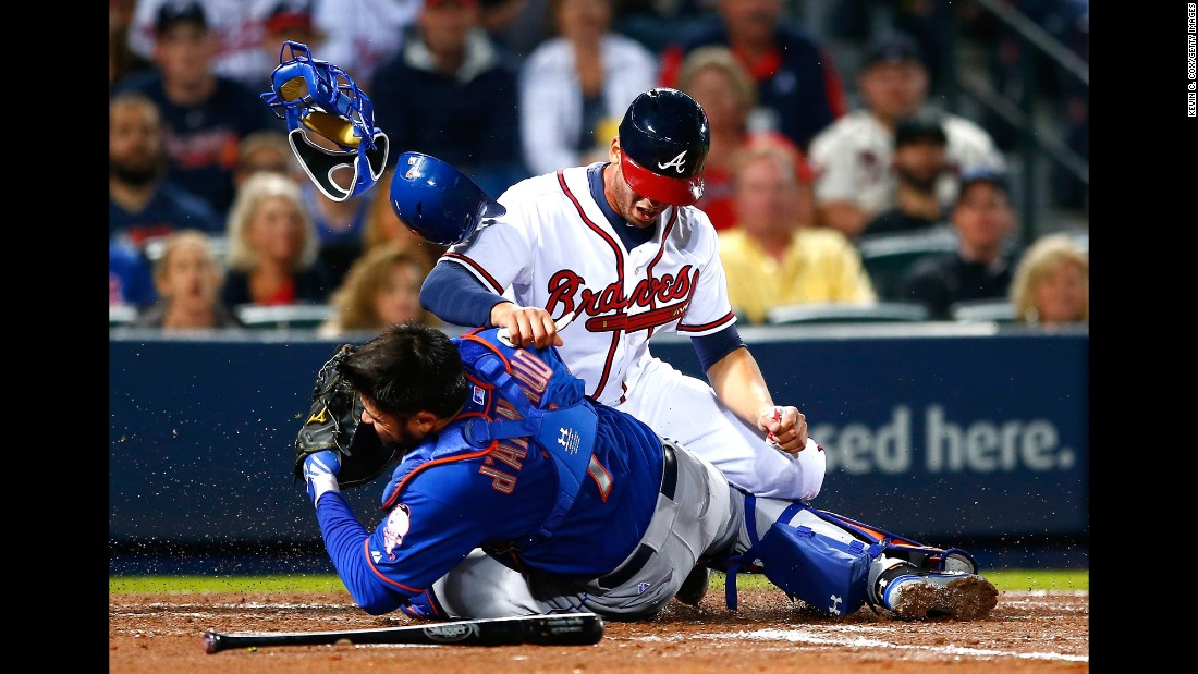 Andrelton Simmons of the Atlanta Braves collides with Travis d'Arnaud of the New York Mets as he is tagged out at home during the Braves' home opener on Friday, April 10.