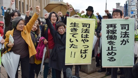 Anti-nuclear activists celebrate after a court issues an injunction against the restarting of two reactors at the Takahama nuclear power plant.