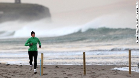 A jogger runs along the shoreline in Portstewart in Northern Ireland, on December 24, 2013. A man and a woman died in separate river incidents on Monday as high winds and heavy rain lashed Britain, disrupting transport as people headed home for the Christmas holidays. AFP PHOTO / PETER MUHLY (Photo credit should read PETER MUHLY/AFP/Getty Images)