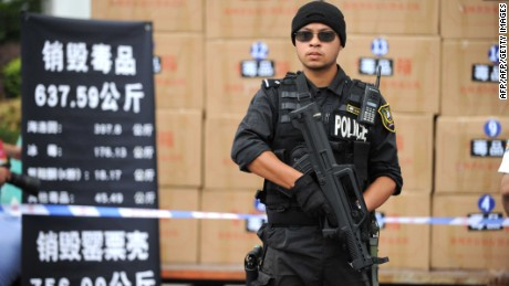 A policeman stands guard as a officials prepare to destroy illegal drugs at a factory in Guiyang, Guizhou Province in 2013.