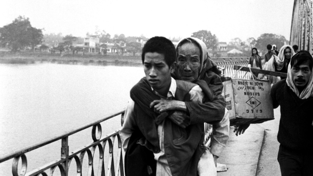 A young refugee carries an elderly woman on his back while crossing a bridge in Hue, Vietnam, in 1968.