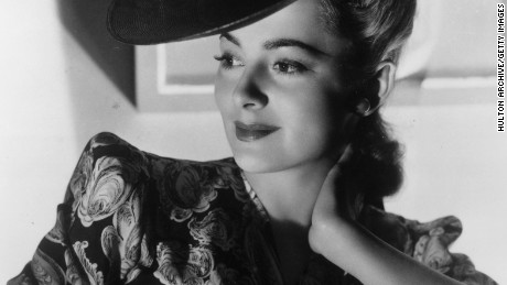 circa 1945:  Portrait of American actor Olivia De Havilland smiling while leaning against her elbow in a dress with puffed sleeves and a dark hat.  (Photo by Hulton Archive/Getty Images)