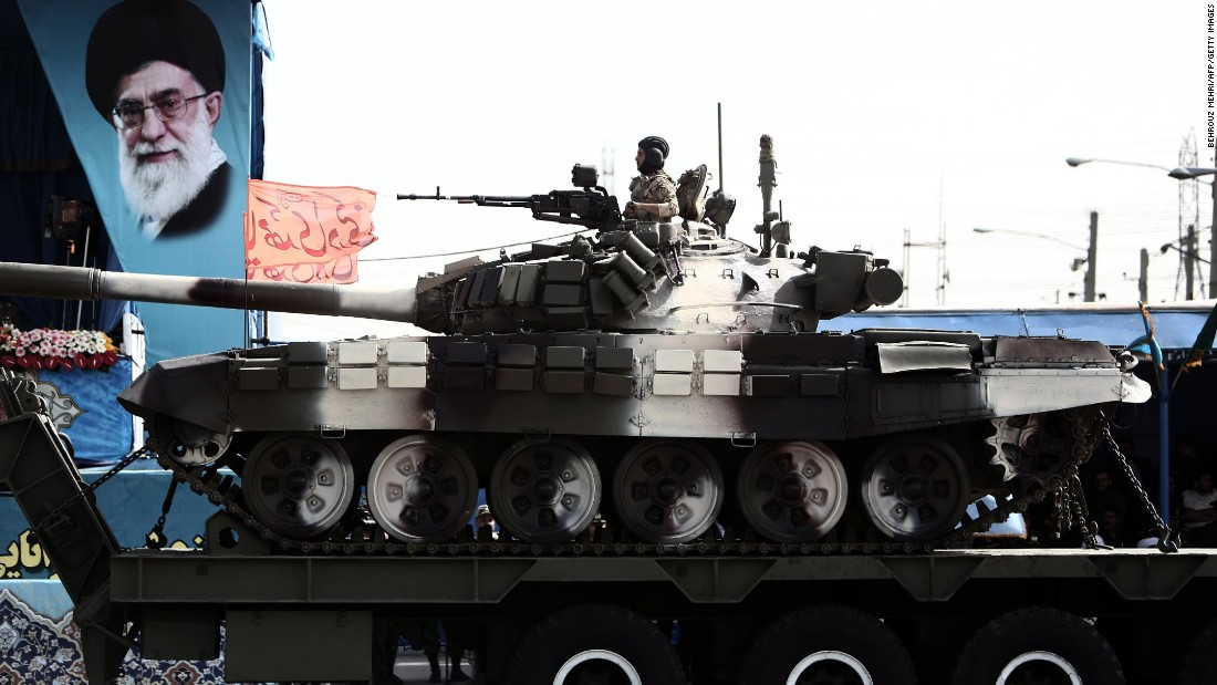A soldier sits atop a T-72 tank as it rolls past a portrait of Supreme Leader Ayatollah Ali Khamenei on April 18.