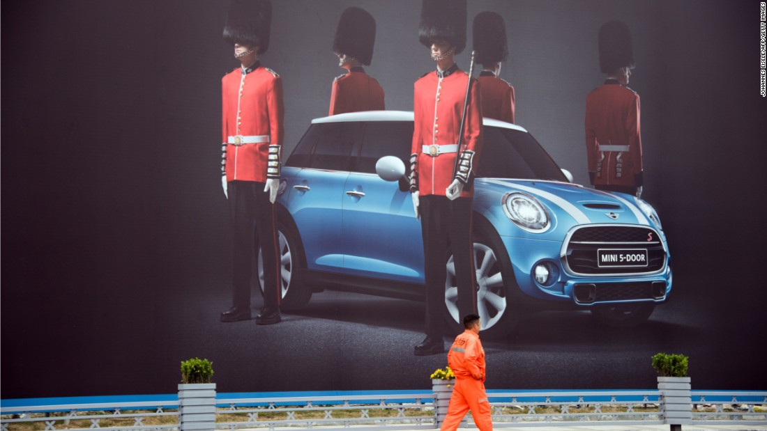 A man walks past a billboard for a Mini 5 door Cooper.