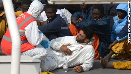 Rescued migrants talk to a member of the Malta Order after a fishing boat carrying migrants capsized off the Libyan coast, is brought ashore along with 23 others retreived by the Italian Coast Guard vessel Bruno Gregoretti at Boiler Wharf, Senglea in Malta on April 20, 2015.