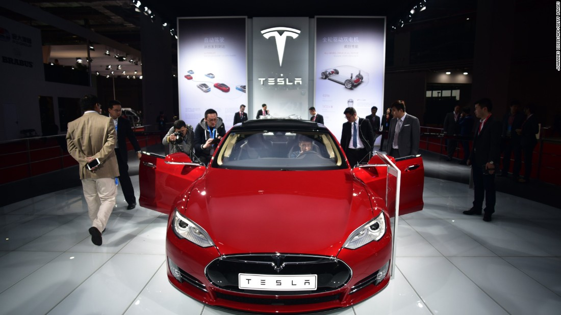 "Visitors try out the driver's seat of a Tesla Model S P85D car displayed at the Shanghai Auto Show. The ""D"" stands for dual motor, which powers front and back wheels, giving it more oomph than the previous model. And it has a range of around 250 miles per charge."