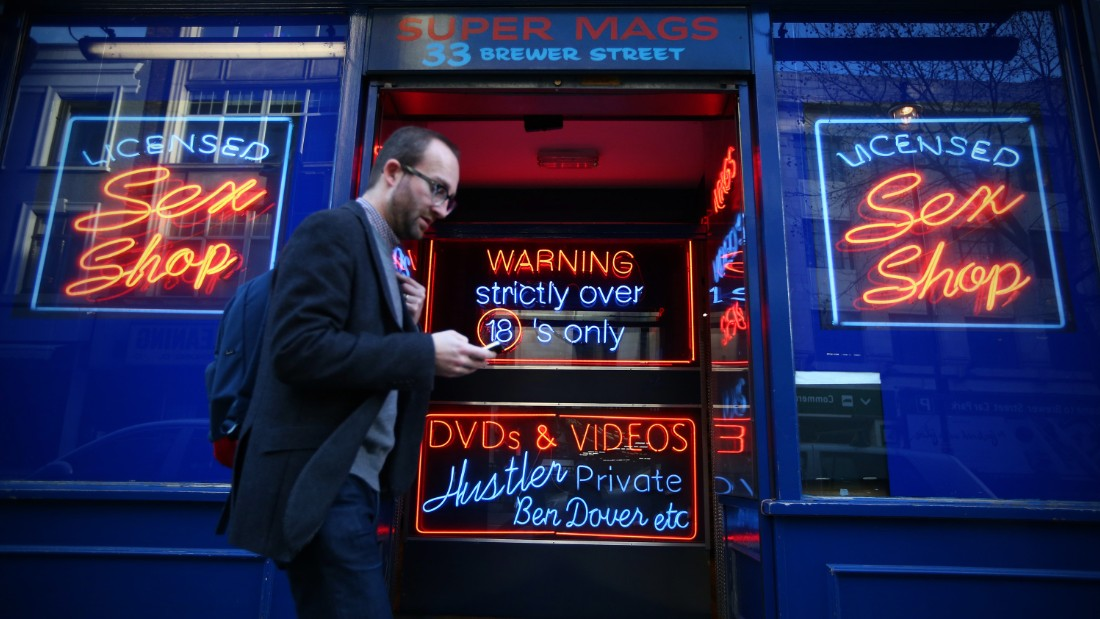 A man walks past a sex shop in Soho in 2015. A growing number of campaigners, including Stephen Fry, are pushing developers and representatives of Westminster Council to preserve the area's unique identity, which they fear is being lost as the area is gradually redeveloped.