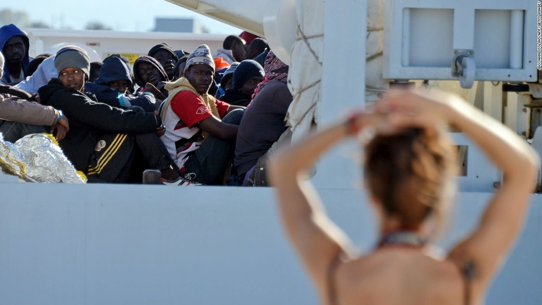 Shipwrecked migrants sit on the deck of a rescue vessel as they arrive in the Italian port of Augusta on Thursday, April 16.