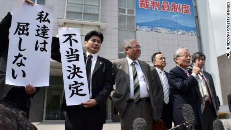 Japanese lawyers show banners with 'unfair ruling' in front of the Kagoshima district court in Kagoshima, Japan's southern island of Kyushu on April 22, 2015.
