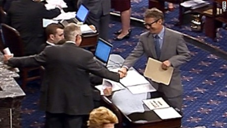 Rand Paul and Harry Reid fist bump while wearing sunglasses on the Senate floor.