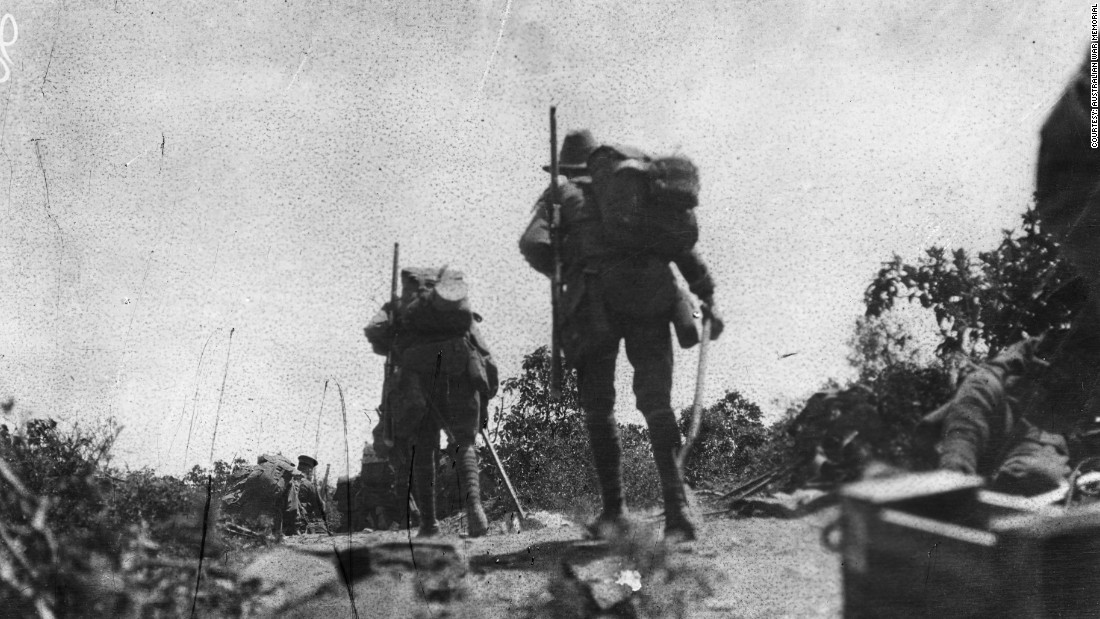 This image shows Australian troops crossing Plugge's Plateau after the landing on 25 April, at about midday. The men in front are thought to be kneeling in the scrub. The troops were under fire from the other side of Shrapnel Valley. This scene is from a captured Turkish trench overlooking the beach at Anzac Cove.