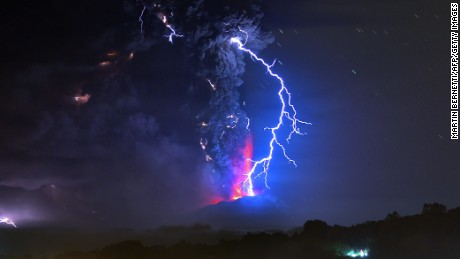 View from Frutillar, southern Chile, of lava spewing from the Calbuco volcano, on April 23, 2015. Chile's Calbuco volcano erupted on Wednesday, spewing a giant funnel of ash high into the sky near the southern port city of Puerto Montt and triggering a red alert. Authorities ordered an evacuation for a 10-kilometer (six-mile) radius around the volcano, which is the second in southern Chile to have a substantial eruption since March 3, when the Villarrica volcano emitted a brief but fiery burst of ash and lava. AFP PHOTO/MARTIN BERNETTI        (Photo credit should read MARTIN BERNETTI/AFP/Getty Images)