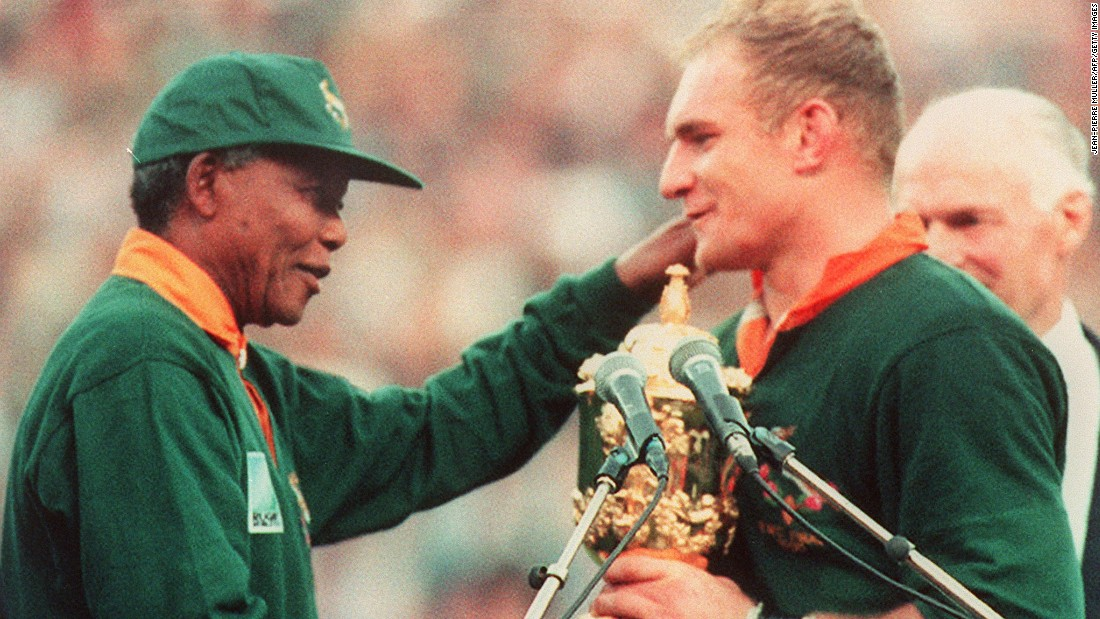 Under the watchful eye of Mandela, captain François Pienaar leads his team to a 15-12 victory over New Zealand in the Rugby World Cup final. Sporting a Springbok jersey and cap, Mandela presents the trophy in front of a huge crowd at Ellis Park, Johannesburg, on June 24, 1995.