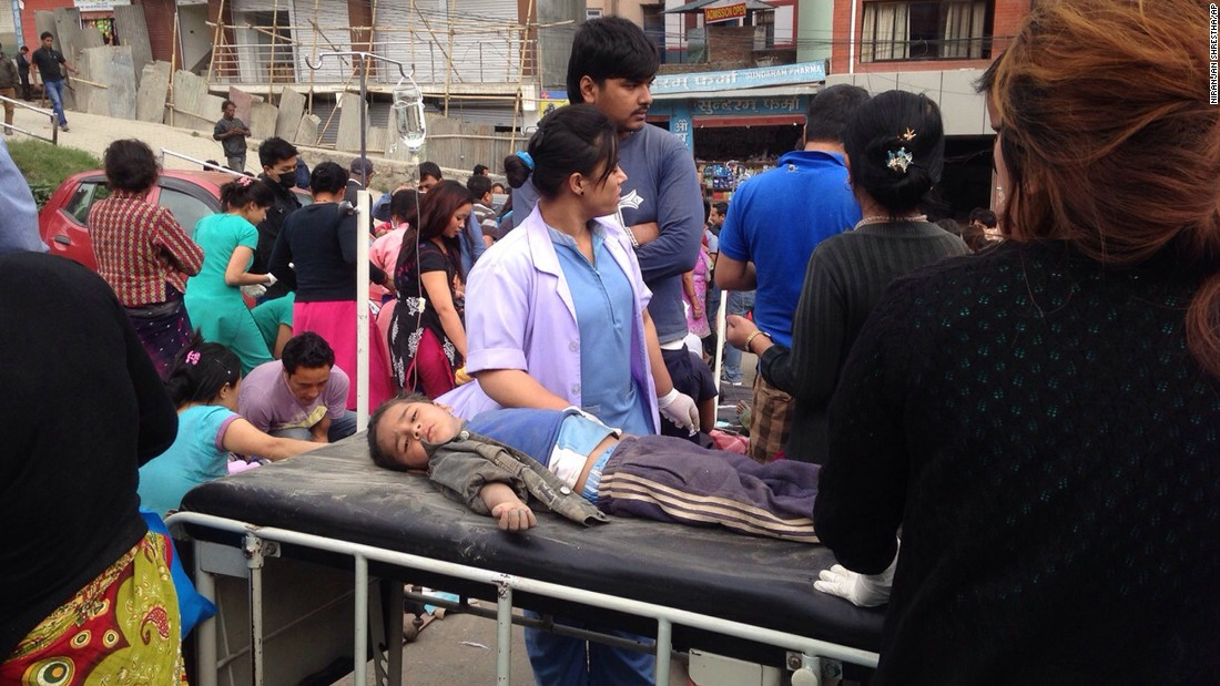 An injured child receives treatment outside Medicare Hospital in Kathmandu on April 25. Residents, after a relentless series of aftershocks, have been remaining outdoors.