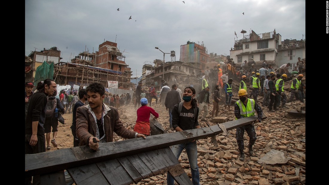 Rescue workers clear debris in Kathmandu while searching for survivors.