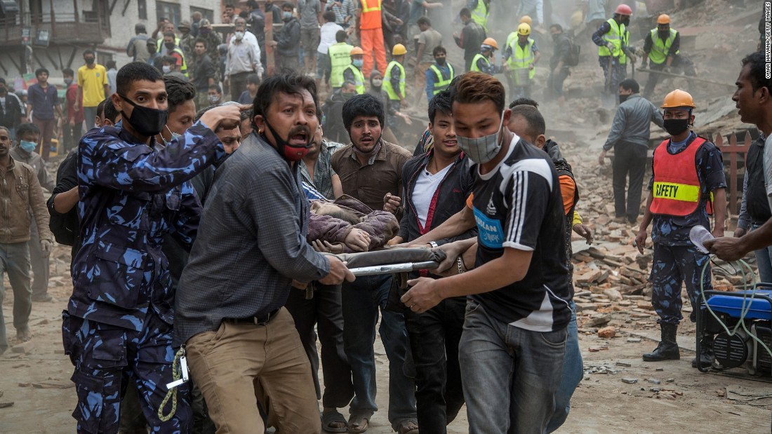 Emergency rescue workers carry a victim from Dharahara after the tower in Kathmandu collapsed on April 25.