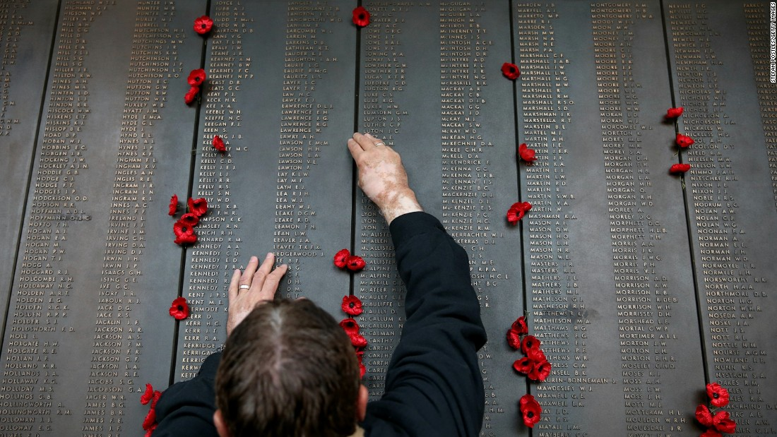 A man places a poppy on the Roll of Honor at the Australian War Memorial in Canberra, Australia.