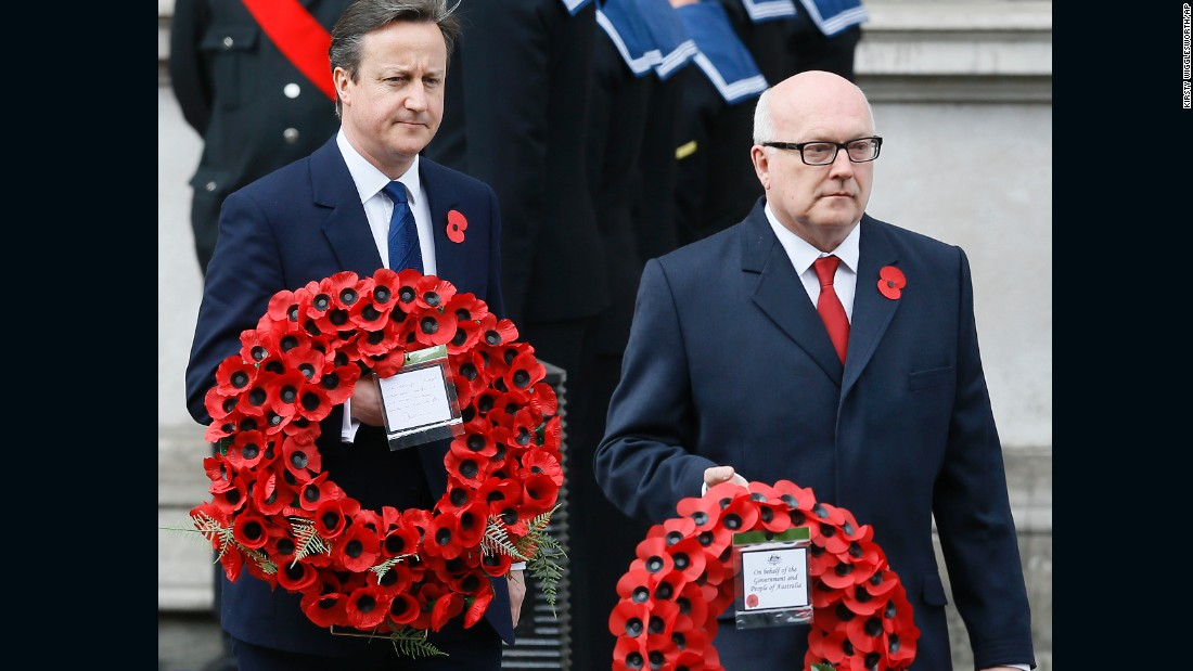 Britain's Prime Minister David Cameron, left, and George Henry Brandis, attorney general for Australia, carry wreaths during a ceremony at the Cenotaph in Whitehall, London,