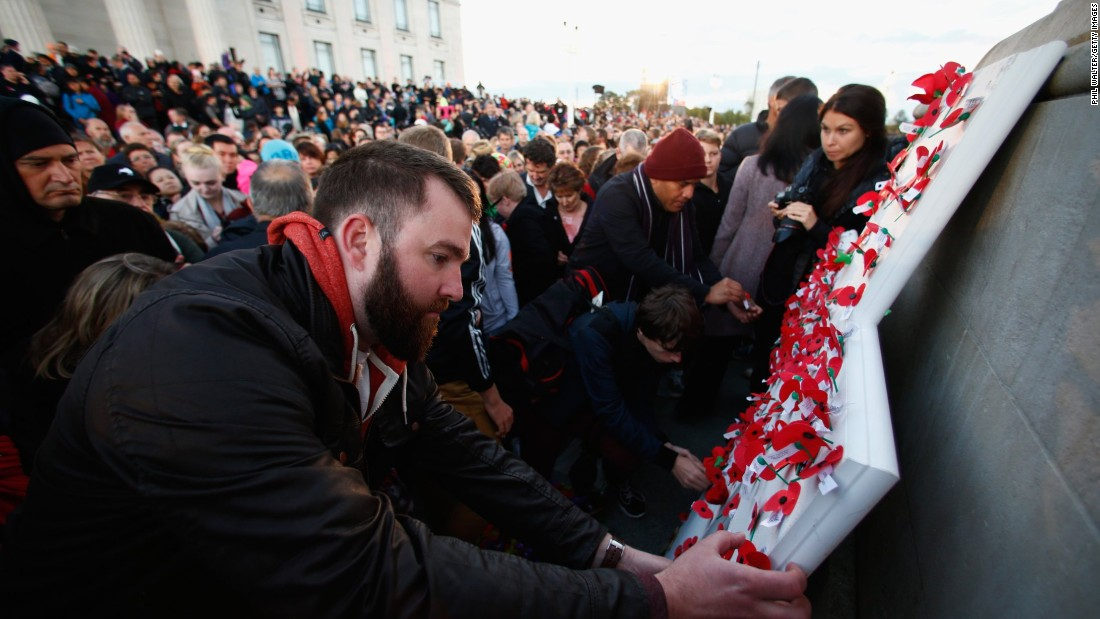 People pin poppies to the Cenotaph following the dawn service at the Auckland War Memorial Museum  in Auckland, New Zealand.