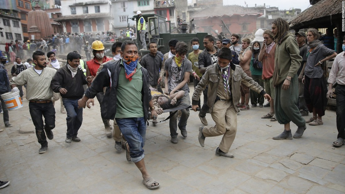 Civilian rescuers carry a person on a stretcher in Kathmandu on April 25.