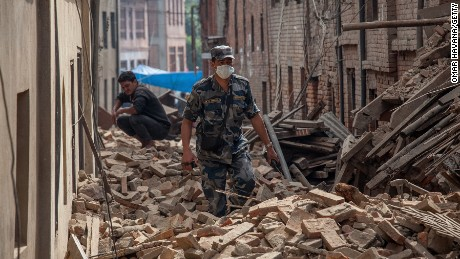Caption:BHAKTAPUR, NEPAL - APRIL 26: A member of police forces walk down a street covered in debris after buildings collapsed on April 26, 2015 in Bhaktapur, Nepal. A major 7.8 earthquake hit Kathmandu mid-day on Saturday, and was followed by multiple aftershocks that triggered avalanches on Mt. Everest that buried mountain climbers in their base camps. Many houses, buildings and temples in the capital were destroyed during the earthquake, leaving thousands dead or trapped under the debris as emergency rescue workers attempt to clear debris and find survivors. (Photo by Omar Havana/Getty Images)