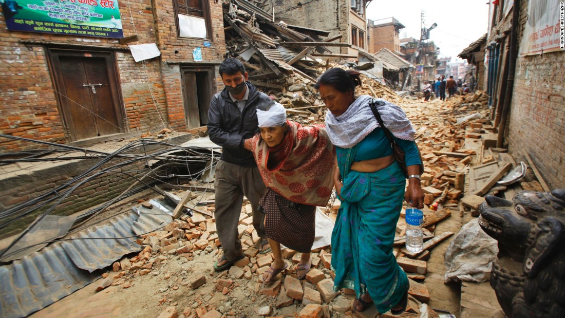 An elderly woman is helped to her home after being treated for her injuries in Bhaktapur on April 26.