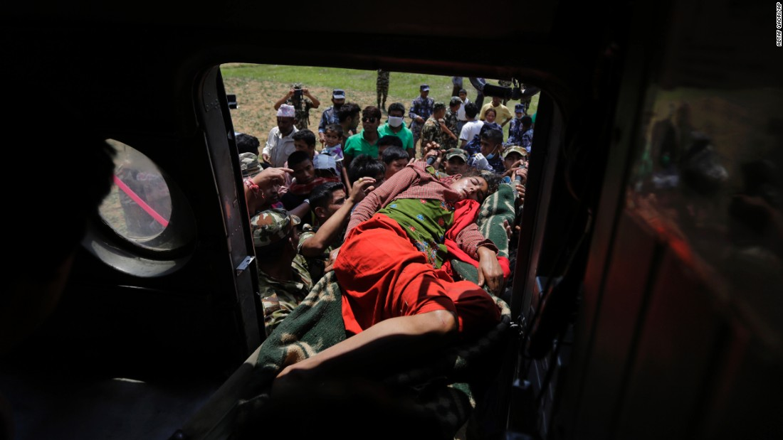 Nepalese soldiers carry a wounded woman to a helicopter as they evacuate people from Trishuli Bazar, Nepal, on April 27.