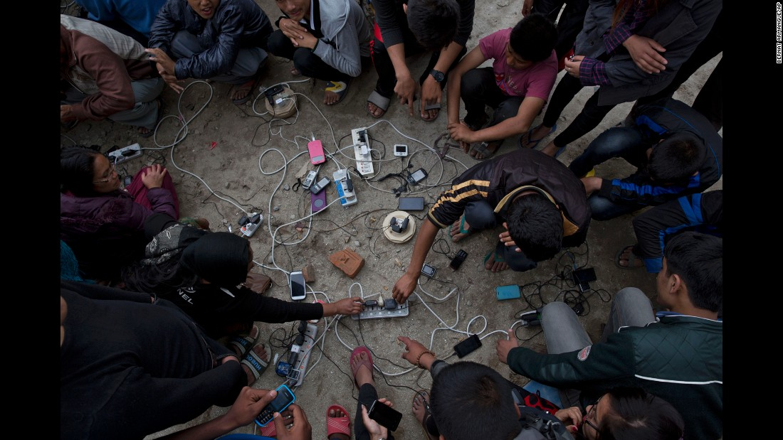 People charge their cell phones in an open area in Kathmandu on April 27.