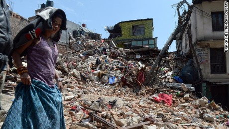 Caption:A Nepalese woman walks past a damaged house in Balaju in Kathmandu on April 27, 2015. International aid groups and governments intensified efforts to get rescuers and supplies into earthquake-hit Nepal on April 26, 2015, but severed communications and landslides in the Himalayan nation posed formidable challenges to the relief effort. As the death toll surpassed 2,000, the US together with several European and Asian nations sent emergency crews to reinforce those scrambling to find survivors in the devastated capital Kathmandu and in rural areas cut off by blocked roads and patchy phone networks. AFP PHOTO/PRAKASH SINGH (Photo credit should read PRAKASH SINGH/AFP/Getty Images)