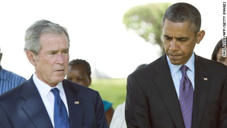 US President Barack Obama (R) and former US President George W. Bush (2nd R) bow their heads on July 2, 2013 alongside victims during a wreath-laying ceremony for the victims of the 1998 US Embassy bombing at the Bombing Memorial at the US Embassy in Dar Es Salaam. Bush is in Tanzania for a forum of regional First Ladies, hosted by his wife Laura, which will also be attended by First Lady Michelle Obama.
