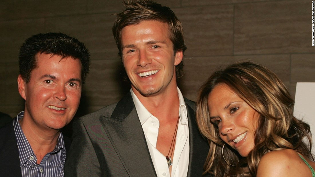 "Here he is pictured with two of the people responsible for helping him become a global phenomenon, transcending his status as a football star: his wife Victoria (right) and ""American Idol"" creator Simon Fuller (left)."