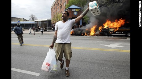 A man carries items from a store as police vehicles burn, Monday, April 27, 2015, after the funeral of Freddie Gray in Baltimore. Gray died from spinal injuries about a week after he was arrested and transported in a Baltimore Police Department van.